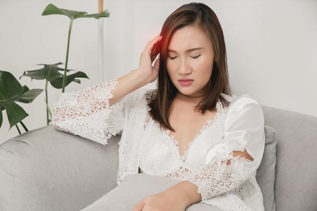Mulheres com dor de cabeça em uma camisola de cetim e um robe branco com renda floral em um sofá cinza Foto Premium