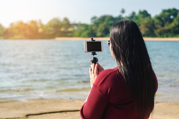 Mulheres, com, esperto, telefone móvel, em, seascape, natureza, fundo Foto Premium