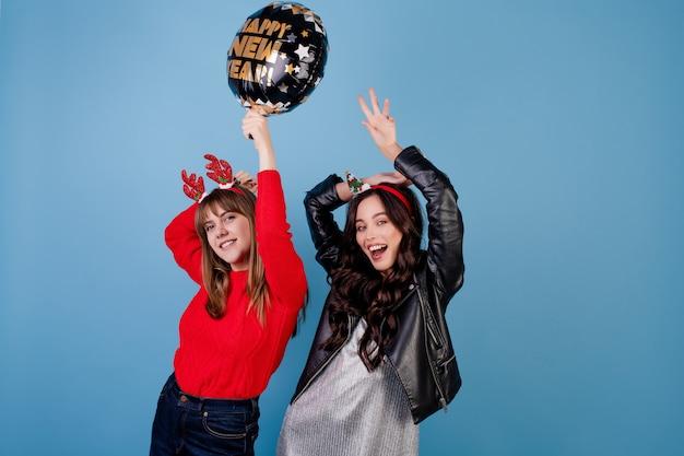 Mulheres com feliz ano novo balão vestindo roupas de inverno Foto Premium
