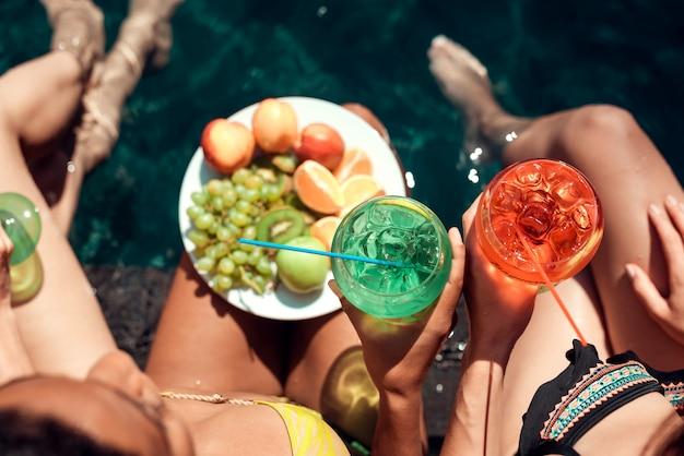 Mulheres com frutas e coquetéis à beira da piscina Foto Premium