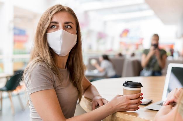 Mulheres com máscara trabalhando e bebendo café Foto gratuita