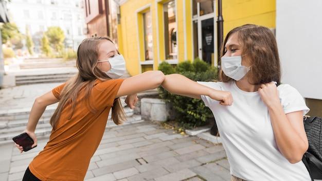Mulheres com máscaras médicas praticando saudação de cotovelo Foto gratuita
