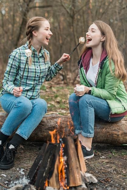 Mulheres comendo marshmallow Foto gratuita