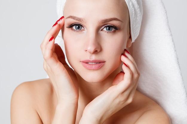 Mulheres da juventude com a toalha em sua cabeça que olha a câmera. interior. cuidados com a pele Foto Premium