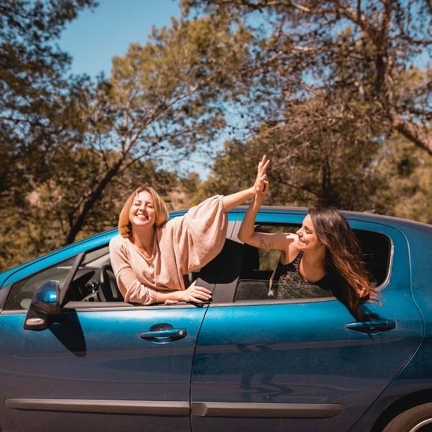 Mulheres de alta fiving no carro Foto gratuita