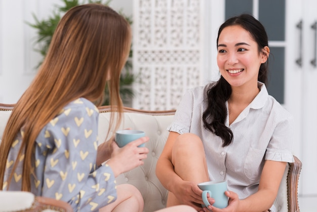 Mulheres de alto ângulo no sofá conversando Foto gratuita