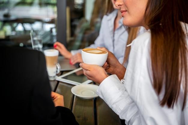 Mulheres de alto ângulo, trabalhando e bebendo café Foto gratuita