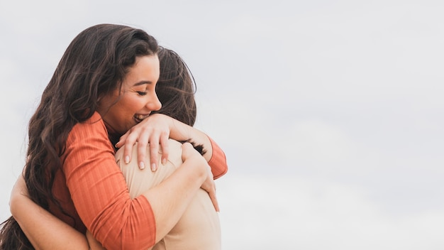 Mulheres de baixo ângulo abraçando Foto gratuita