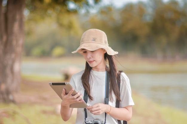Mulheres de beleza segurando o tablet com câmera viajam tirar foto Foto Premium