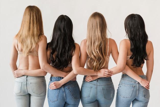 Mulheres de cabelos compridos, vestindo sutiãs ficar juntos e abraçando Foto gratuita