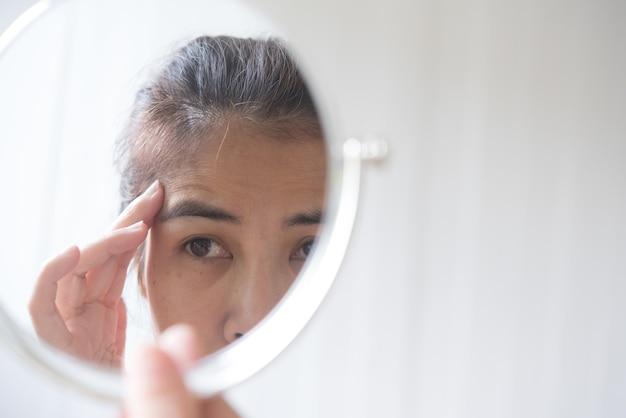 Mulheres de meia-idade olham para o espelho para ver as rugas faciais. Foto Premium