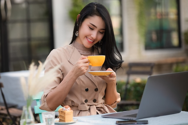 Mulheres de negócios asiáticos bebendo café e bolo Foto Premium