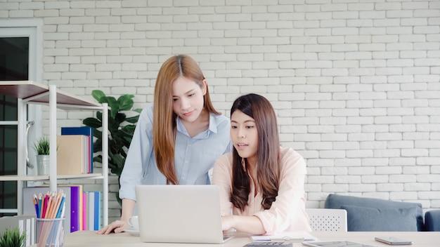 Mulheres de negócios asiáticos criativos inteligentes atraentes em casual desgaste inteligente trabalhando no laptop enquanto está sentado Foto gratuita