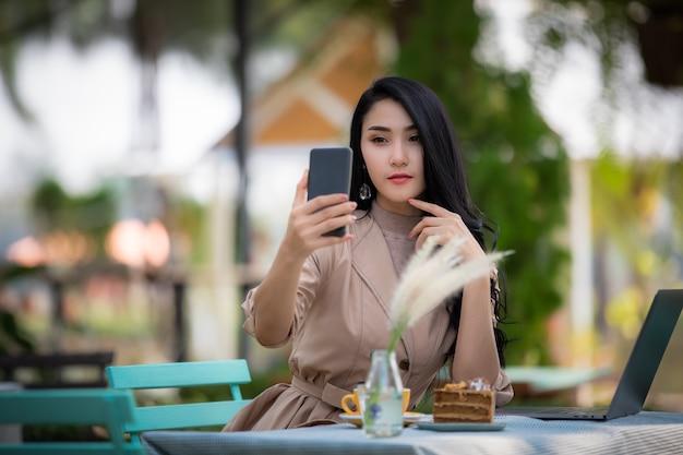 Mulheres de negócios asiáticos usando selfie no smartphone e laptop bolo e café em cima da mesa no jardim Foto Premium
