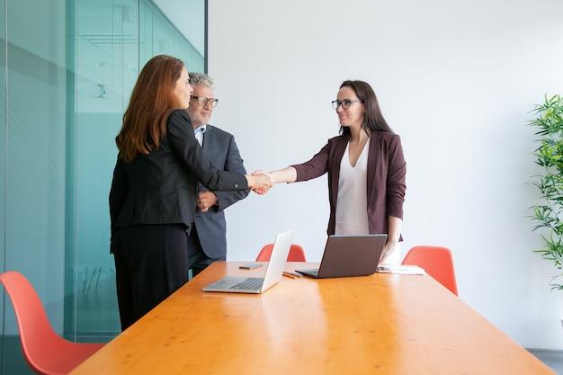 Mulheres de negócios bem-sucedidas se cumprimentam e se cumprimentam Foto gratuita