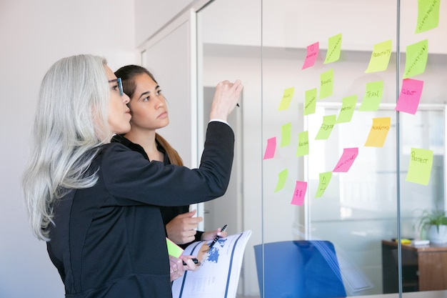 Mulheres de negócios concentradas olhando adesivos na parede de vidro. trabalhadora de cabelos grisalhos focada fazendo anotações para a estratégia ou plano do projeto Foto gratuita