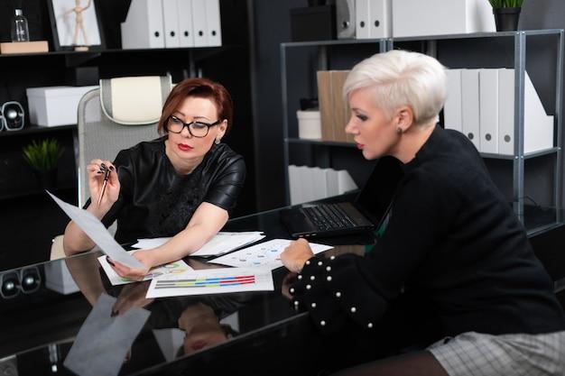 Mulheres de negócios discutem diagramas na mesa no escritório Foto Premium