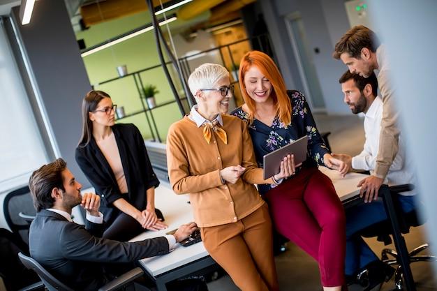 Mulheres de negócios felizes trabalhando juntos on-line em um tablet digital no escritório Foto Premium