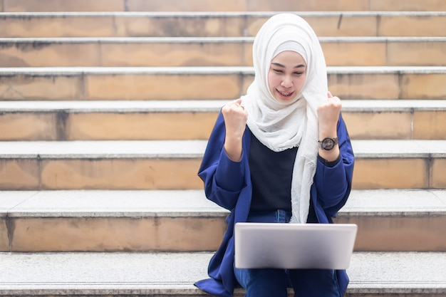 Mulheres de negócios muçulmanas felizes no hijab com o portátil que trabalha ao ar livre. Foto Premium