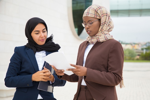 Mulheres de negócios muçulmano discutindo texto do contrato Foto gratuita