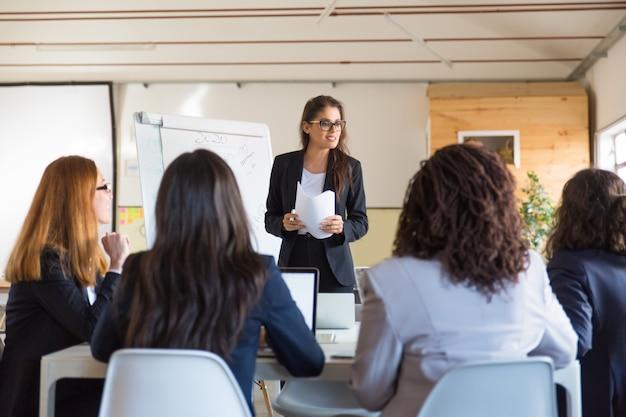Mulheres de negócios olhando alto-falante com papéis Foto gratuita