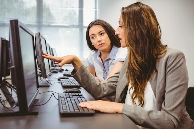 Mulheres de negócios sérias olhando a tela do computador juntos ...