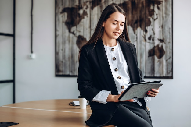 Mulheres de negócios trabalhando em um tablet se espalha sobre uma mesa, no escritório Foto Premium
