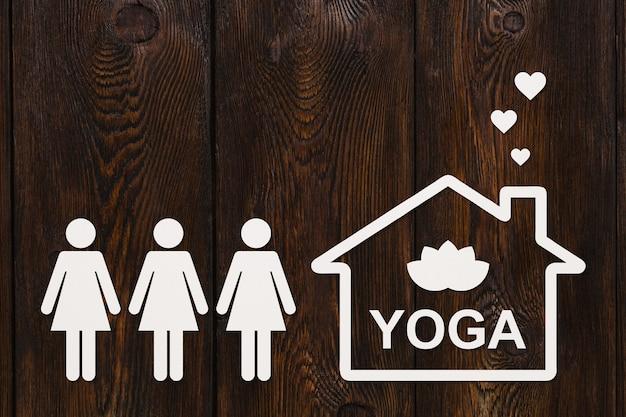 Mulheres de papel e casa com texto ioga dentro de madeira Foto Premium
