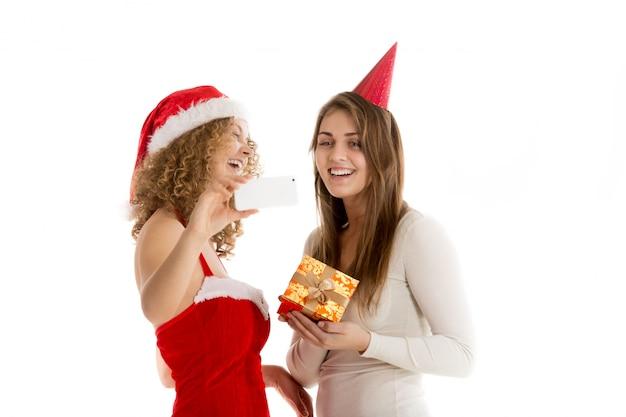 Mulheres de sorriso com um presente Foto gratuita