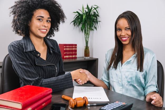 Mulheres de sorriso pretas que agitam as mãos na tabela com equipamentos Foto gratuita