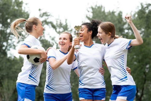 Mulheres de tiro médio segurando uma taça de ouro Foto gratuita