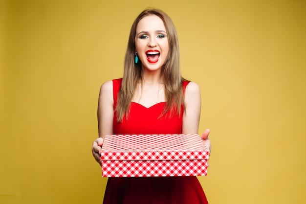 Mulheres de vestido vermelho, sorrindo e segurando presente para o ano novo. Foto Premium