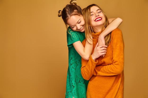 Mulheres despreocupadas isoladas na parede dourada modelos positivos posando com seus vestidos Foto gratuita