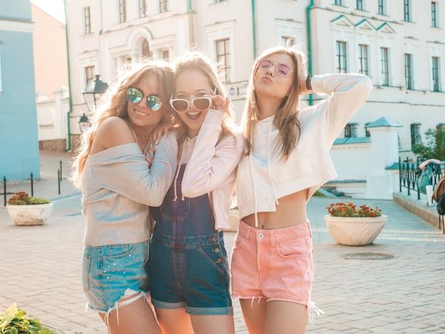 Mulheres despreocupadas sexy, posando no fundo da rua, abraçando ao pôr do sol Foto gratuita