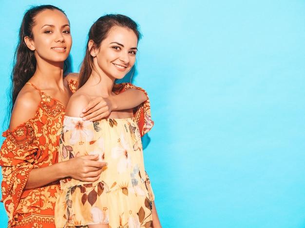 Mulheres despreocupadas sexy posando perto da parede azul. divertindo-se e abraçando. modelos mostra bom relacionamento. mulher sem maquiagem Foto gratuita