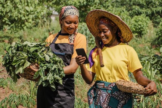 Mulheres do campo navegando juntas em um telefone Foto Premium