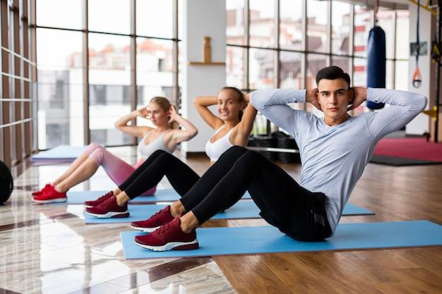 Mulheres e homem exercitando na academia Foto gratuita