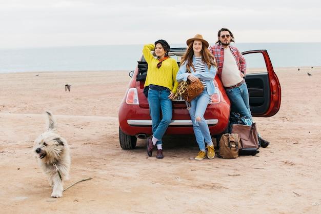 Mulheres e homem perto de carro e cachorro correndo na praia Foto gratuita