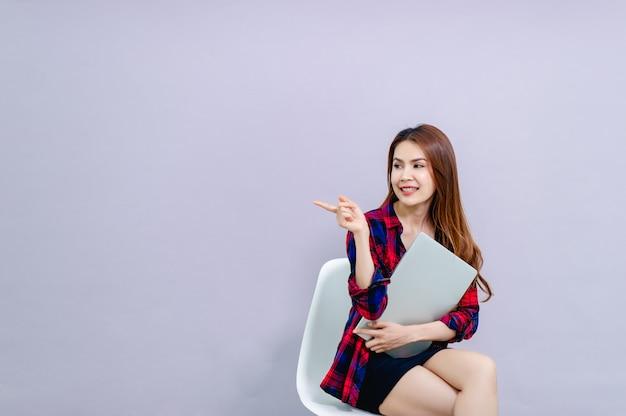Mulheres e laptops sentados e abraçando o laptop alegremente no trabalho Foto Premium