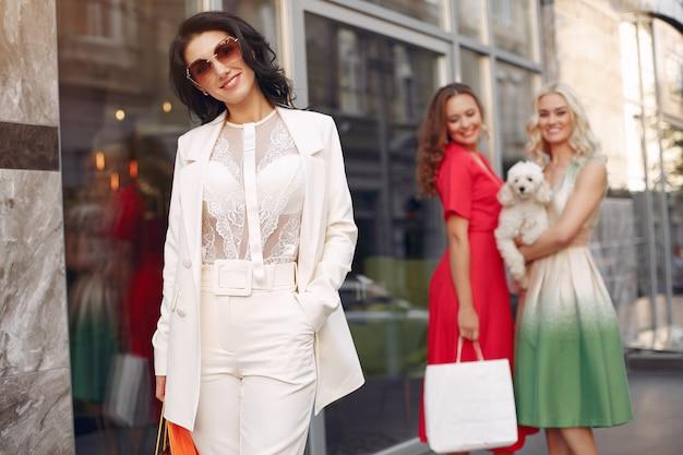Mulheres elegantes com sacolas de compras em uma cidade Foto gratuita