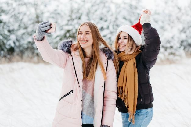Mulheres, em, chapéu santa, levando, selfie, em, inverno, floresta Foto gratuita