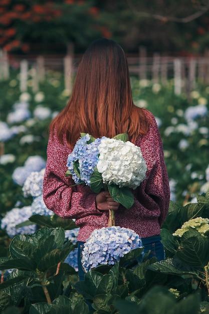 Mulheres em pé segurando flores de hortênsia Foto Premium