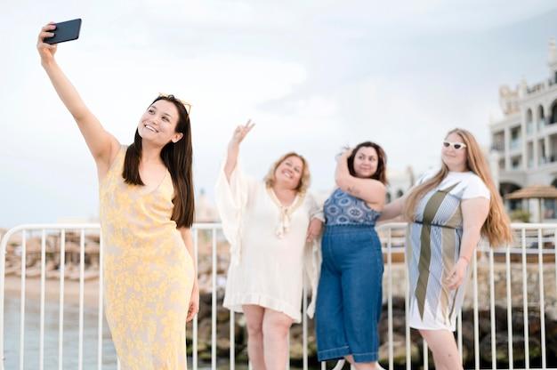 Mulheres em roupas casuais, tomando uma selfie Foto gratuita