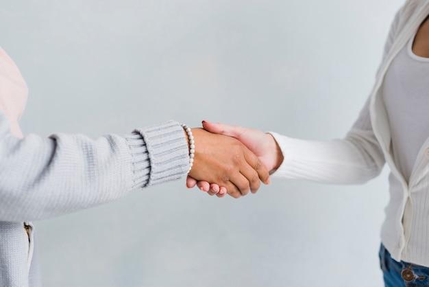 Mulheres, em, roupas pálidas, apertar mão, em, saudação Foto gratuita