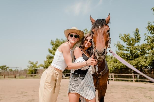 Mulheres, em, um, campo, andar, com, um, cavalo Foto Premium