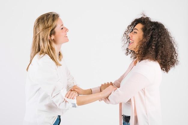 Mulheres encantadoras agarrando braços Foto gratuita