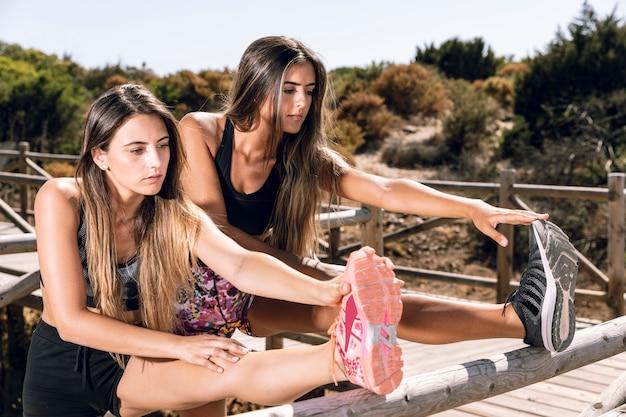 Mulheres, esticar, pernas, ligado, cais Foto gratuita