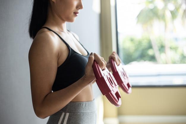 Mulheres exercitando com duas placas de peso com halteres Foto gratuita