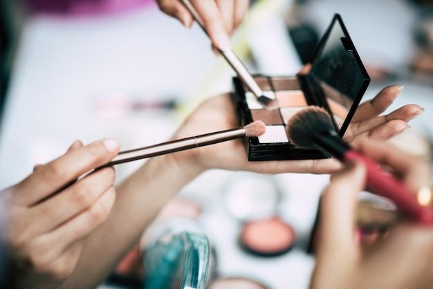 Mulheres, fazendo, maquiagem, com, escova, e, cosmético Foto gratuita