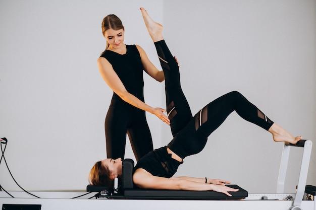 Mulheres fazendo pilates em um reformador Foto gratuita
